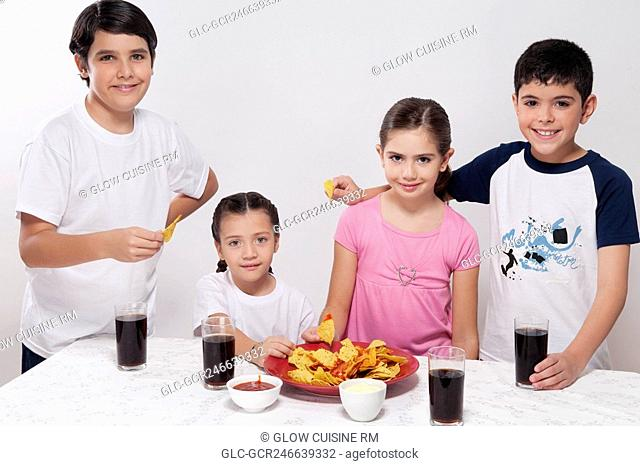 Portrait of two boys and two girls eating nachos from a platter