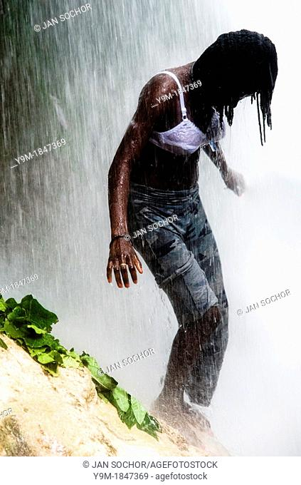 A young Haitian girl performing the cleaning and spiritual ritual right under the Saut d'Eau waterfall in Ville Bonheur, Haiti, July 16