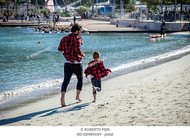Father and son running along beach, rear view