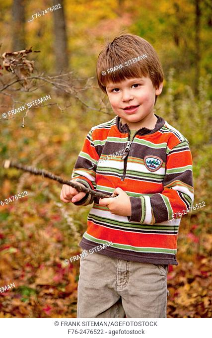 Portrait of a 3 year old boy holding a stick while standing outdoors in the fall