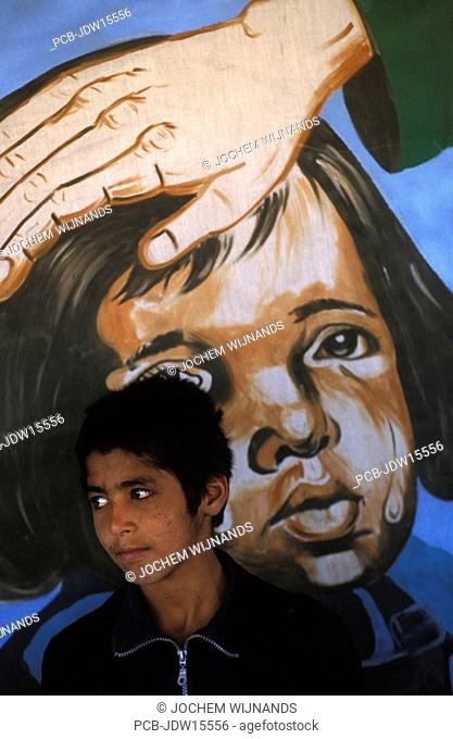 Kabul, portrait of a boy in front of a painting which claims the government is taking care of the Afghan children