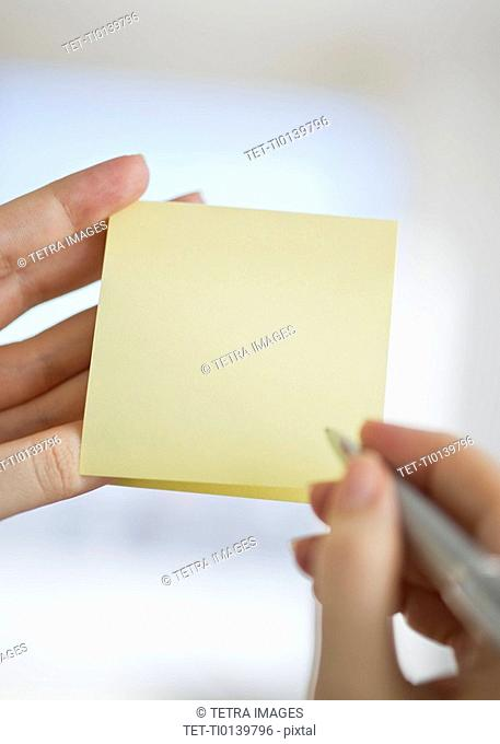 Hands holding notepad and pen
