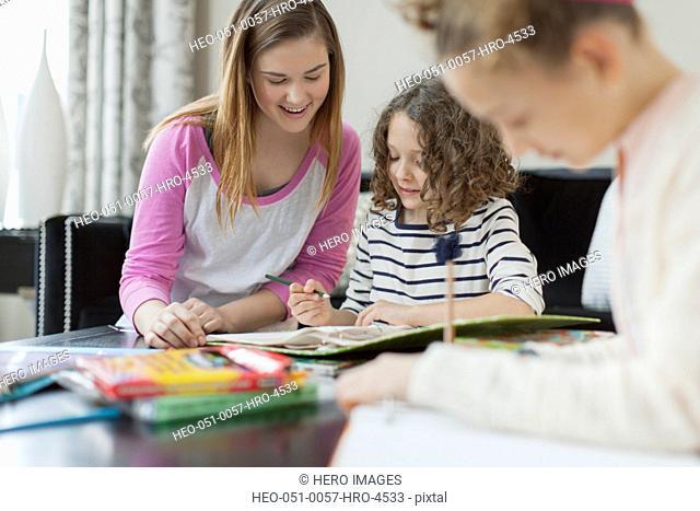 Babysitter helping girls with homework