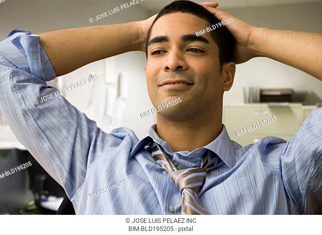 Mixed race businessman with hands on head