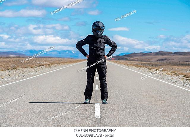 Woman in motorbike clothes standing in the middle of Route 40 - the longest road in South America, El Chalten, Route 40, Santa Cruz province, Argentina