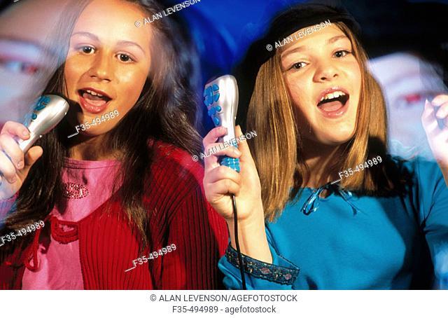 Young girls having fun with sing along with karaoke machine