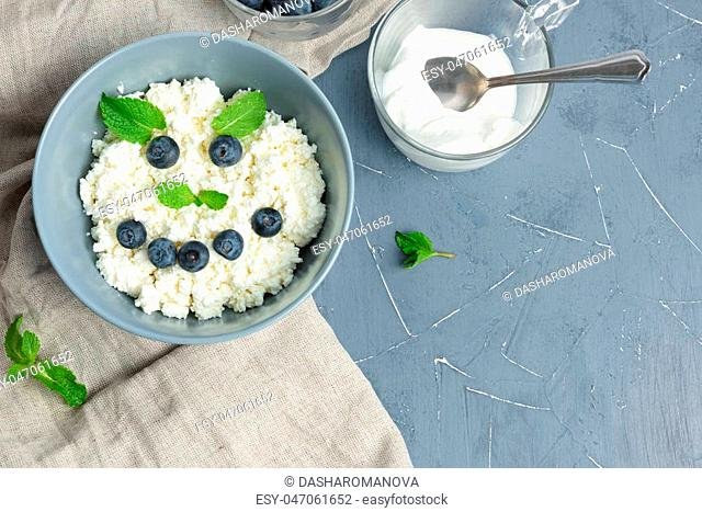 Fresh cottage cheese with juicy blueberries and mint, dietary breakfast for summer time. Smile face