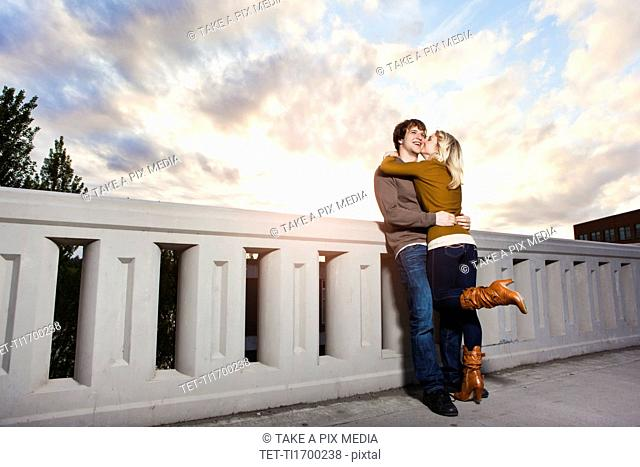 Young couple kissing on bridge