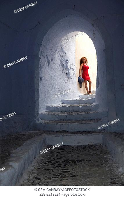 Woman posing at a passageway in Pyrgos town, Santorini, Cyclades Islands, Greek Islands, Greece, Europe