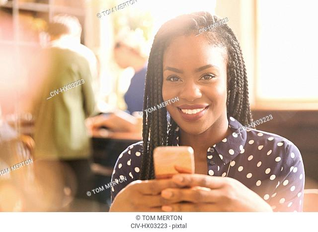 Portrait smiling African woman texting with cell phone in cafe