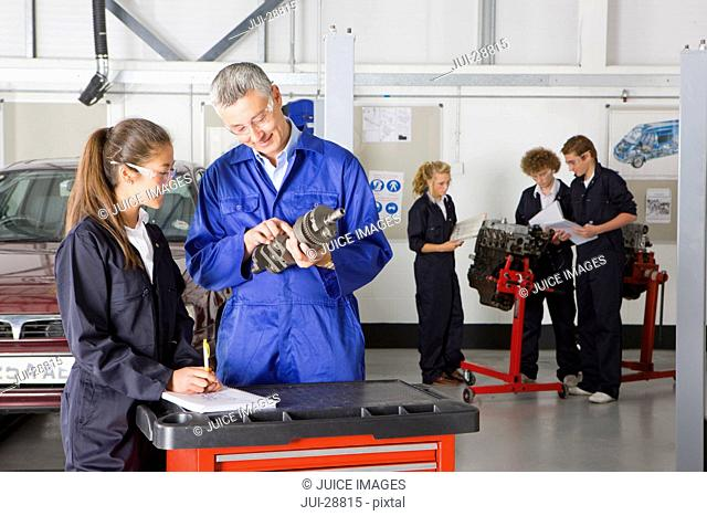 Teacher with auto part teaching student automotive trade in vocational school