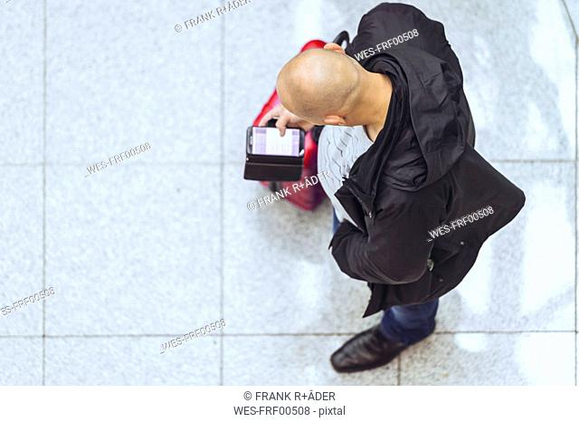 Man with bald head looking at smartphone