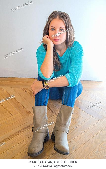 Young woman sitting on wooden floor, looking at the camera