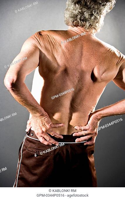 Rear view of senior man with arthritis back pain, studio shot