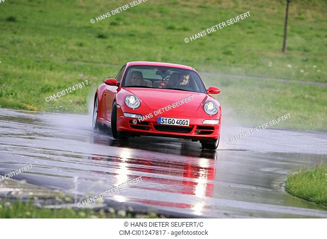 Porsche 911 Carrera 4S, model year 2005-, red, driving, diagonal from the front, frontal view, test track, Aquaplaning