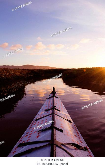 Personal perspective of kayak on river at sunset, Morro Bay, California, USA