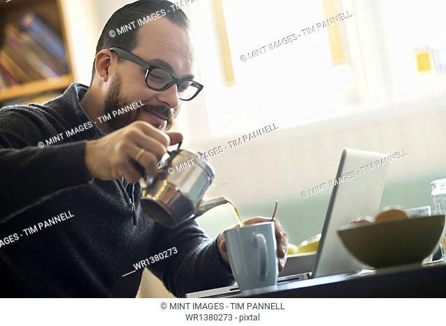 A bearded man having a drink of coffee. An open laptop computer on the counter