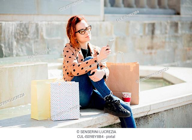 Female shopper using smartphone in front of fountain, Arezzo, Toscana, Italy
