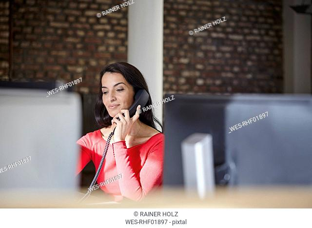 Businesswoman sitting in office, making a call