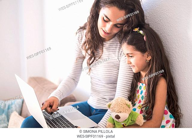 Teenage girl and her little sister using laptop