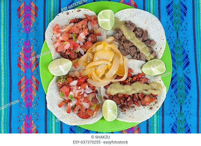 High angle shot of taco plate display of four corn tortillas with different kinds of barbecued meat, salsa, limes and onion on a decorative blue tablecloth