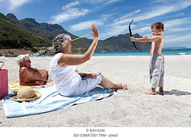 Boy shooting grandmother with toy arrow