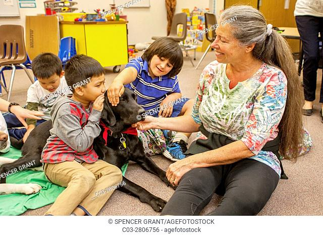 Multiracial young students hug a therapy dog on the floor of an elementary school classroom in Mission Viejo, CA. Note teacher