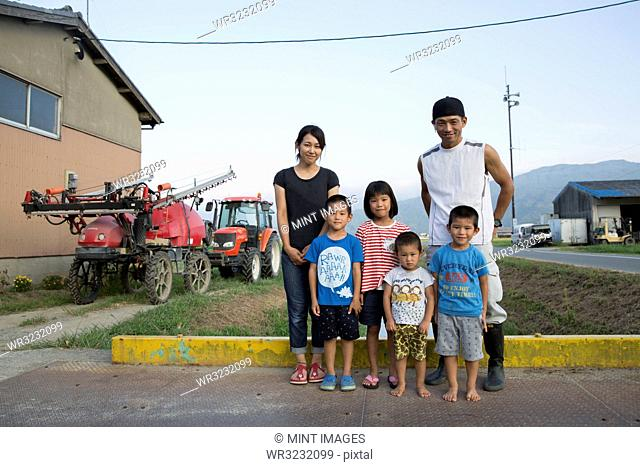 Portrait of Japanese farmer, his wife and four children standing in their yard