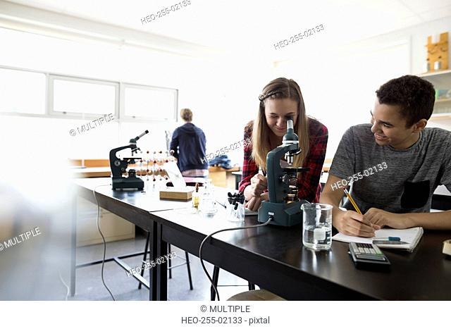 High school students using microscope science laboratory classroom