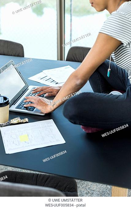 Young woman sitting on conference table using laptop