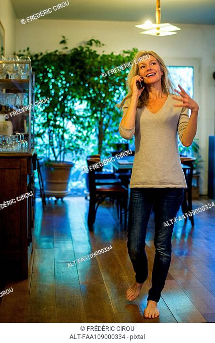 Woman talking on cell phone at home