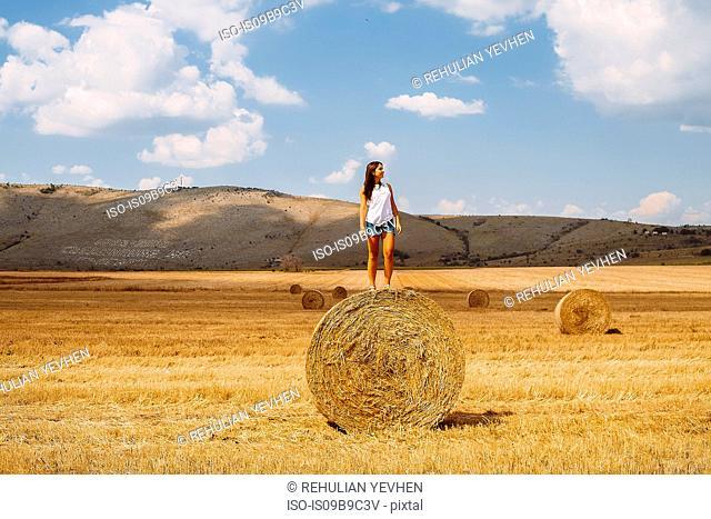 Woman standing on top of hay bale looking away