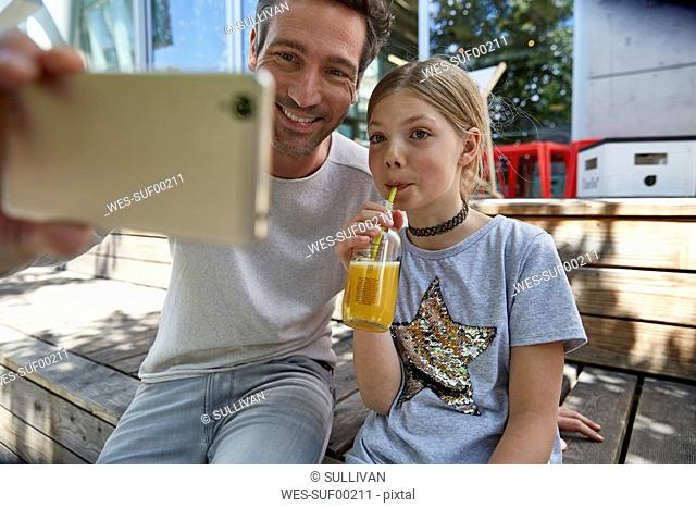 Happy father and daughter taking a selfie at an outdoor cafe
