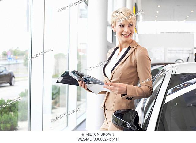 Woman reading catalogue in showroom of car dealership