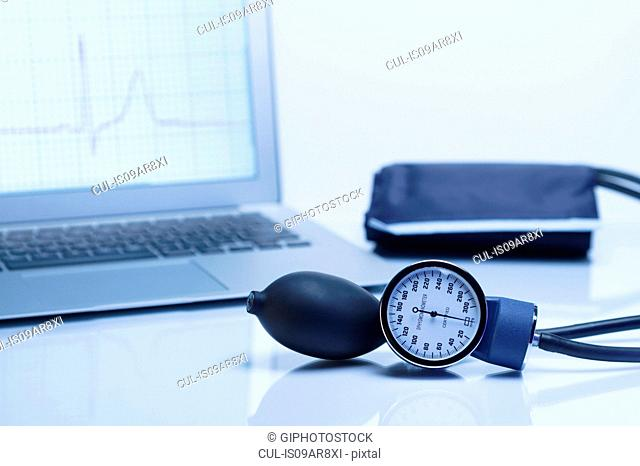 Modern cardiology. Blood pressure gauge with a laptop computer displaying an ECG trace