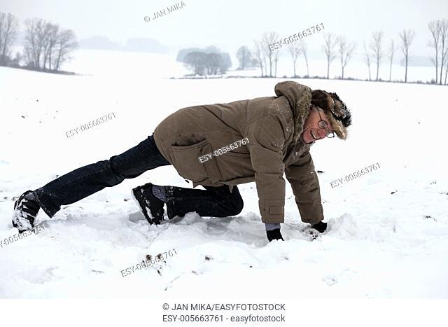Active senior man exercising on snow in winter