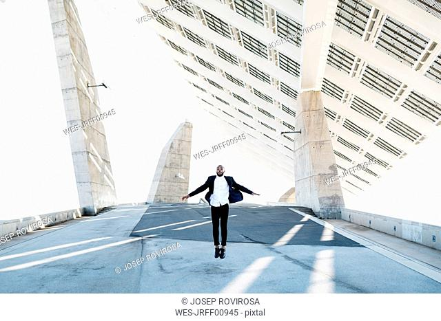 Vital businessman jumping under solar panels