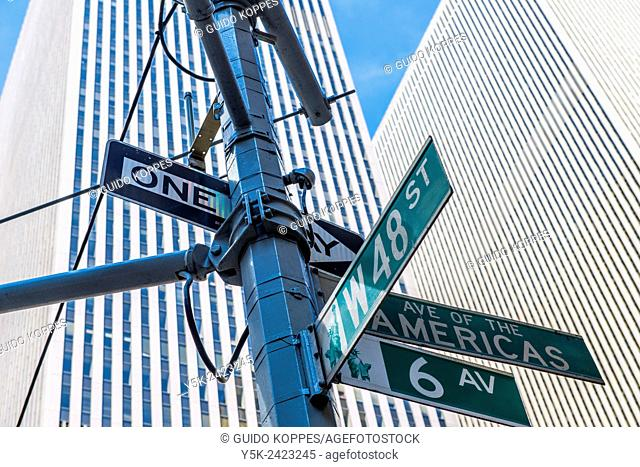 New York, USA. Lamppost and street signs on the corner of 6th Avenue & West 48th Street, Manhattan, in front of a skyscraper
