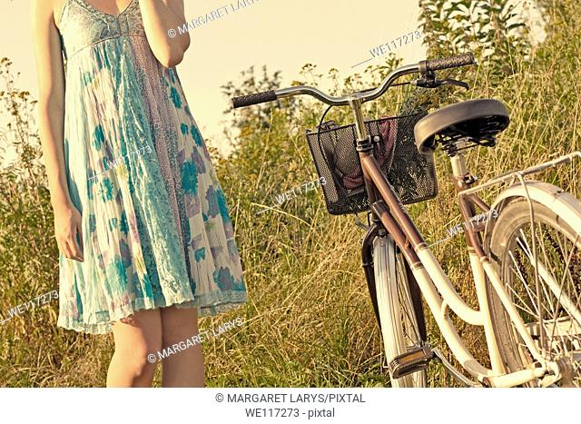 A young girl in a blue dress with a vintage bike in the meadow, waiting