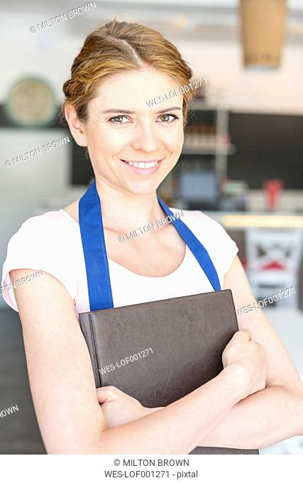 Smiling waitress in cafe holding menu