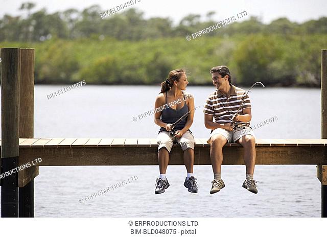 Hispanic couple fishing on pier