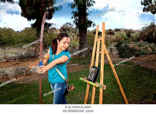 Young woman in garden watching digital tablet practicing archery