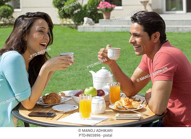 India, Man and woman drinking coffee at breakfast table
