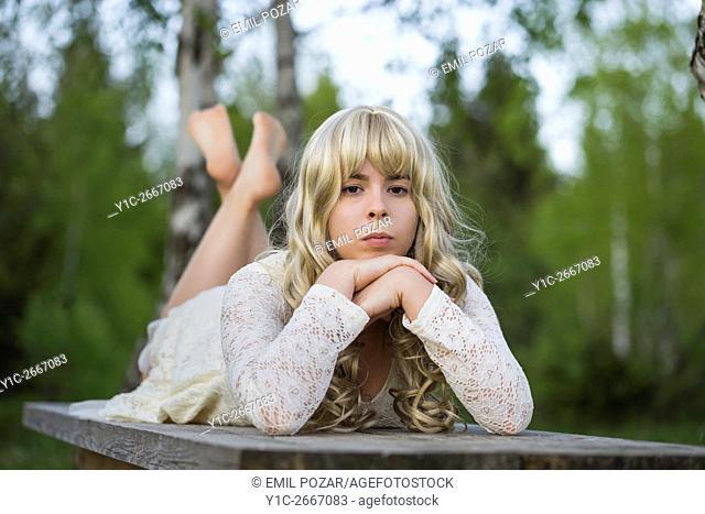 Teen girl lying atop wooden desk