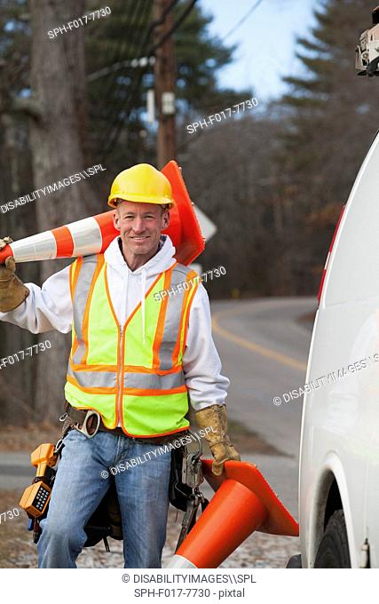 Communications worker moving traffic cones around his truck