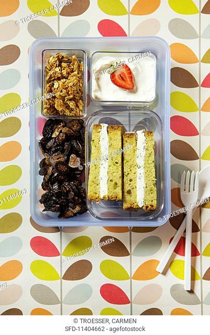 A sandwich, dried fruit, crunchy muesli and a yoghurt in a plastic box