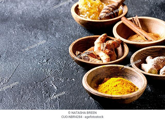 Ingredients for turmeric latte. Ground turmeric, curcuma root, cinnamon, ginger, honeycombs in wooden bowls over black texture background