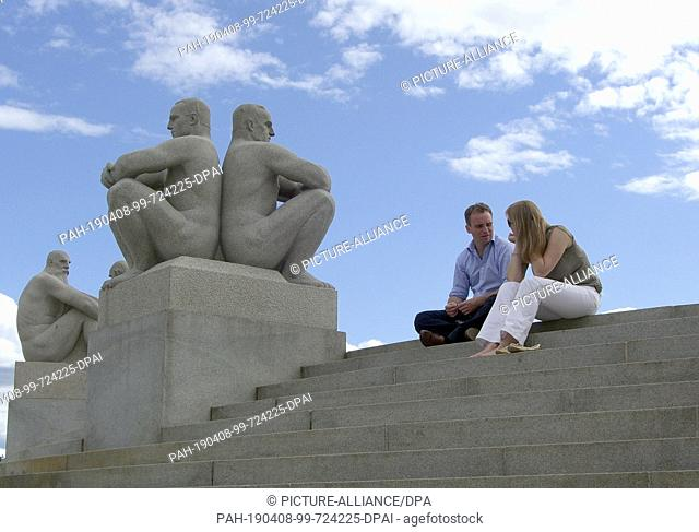"""05 June 2013, Norway, Oslo: Visitors sit on the steps in Vigelandspark next to the sculpture """"""""Two young men, sitting back to back"""""""""""