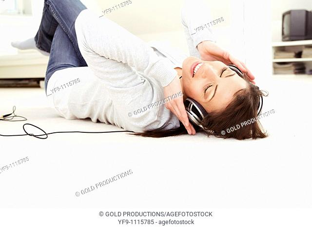 Young woman listening music lying on floor