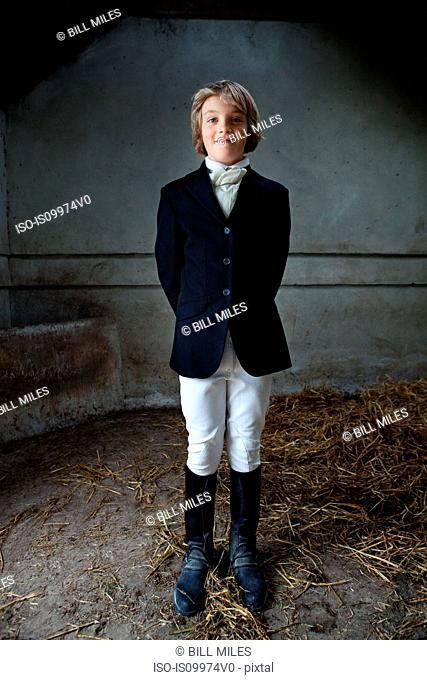 Boy standing in horse riding clothes in stable